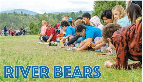 Students add up how many pounds of food they found while pretending to be bears along the Flathead River.