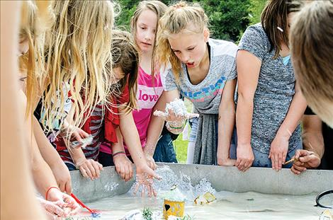 At the 32nd annual River Honoring, children use sand to see how rivers erode.
