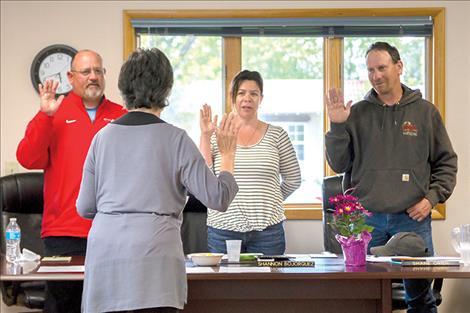 Recently elected trustees Tony Muzquiz, Shannon Bojorquez and Shane Orien take the oath of office at Wednesday night's meeting of the Polson School Board.