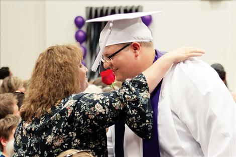 Charlo graduate Dylan Stevens shares a rose and a hug with a loved one.
