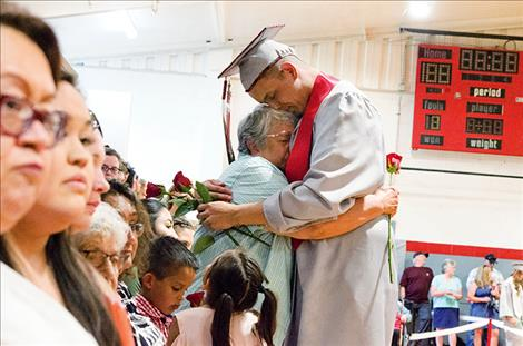 Rory Bird hugs a family member during the rose ceremony where graduates honor important people in their lives.