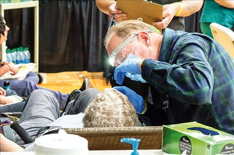A Salish Kootenai College dentist checks to see if a woman has any dental issues at one of the booths.