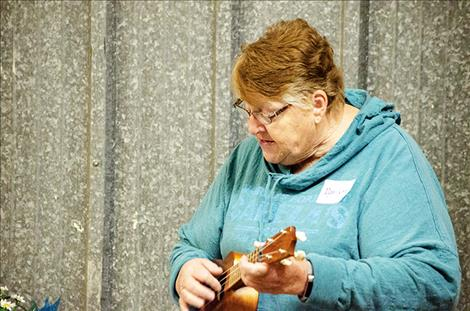 Volunteer Marilynn Tanner plays the ukulele at the celebration.