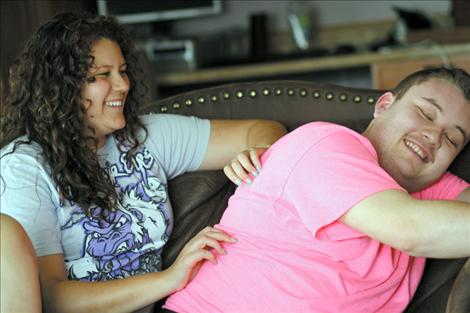 Jake and his 16-year-old sister Jenna smile and laugh during a back rub turned tickle-fight at the Janssen residence.