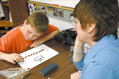 An 11-year-old Jake counts pennies in April 2005 with his former tutor MichalAnn Stedje. Eight years later, Jake is preparing to graduate this spring with his classmates.