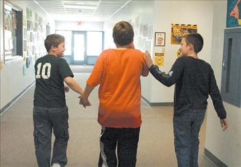 A couple of Jake's classmates lead him down the hallway to play outside in April 2005. Jake's classmates have supported and protected Jake during their school years.