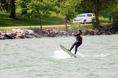 A kite surfer takes full advantage of blustery conditions on Flathead Lake on Saturday.
