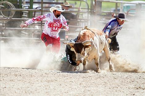 Rob Zolman/Valley Journal Lil' Red drags rider Carnell Smith as bullfighters Austin Wagner and Bo Herak race to his rescue.