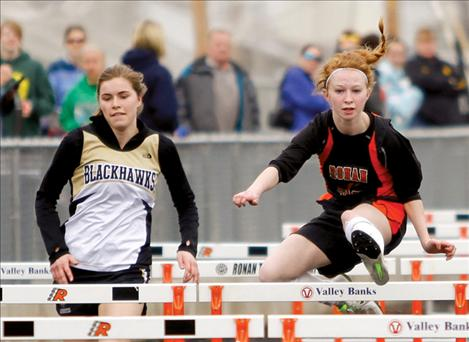 Alex Dennis flies over a hurdle in front of a Seeley-Swan runner at the Ronan Invitational last month.