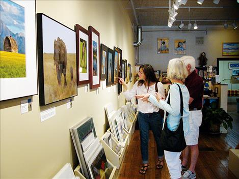 "Visitors peruse a wall of photography at last week's artist reception for the ""Let Me Tell You My Story"" exhibit. The exhibit is currently on display at the Sandpiper Gallery in Polson."