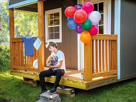 Iliff plays the guitar on the porch of his gifted recording studio during a celebration picnic held in his honor.