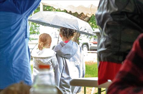 Children watch the rain from under an umbrella.