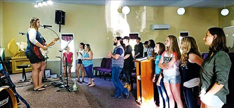 Youth group members worship and sing songs at the Cornerstone Faith Center.