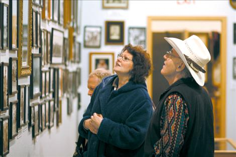 Bud Cheff Jr. tells visitors Larry and Cecilia Hollinder the stories behind hundreds of black and while photographs adorning the museum walls. Many artifacts come from either Cheff's close family or the personal collection he started when he was a child.