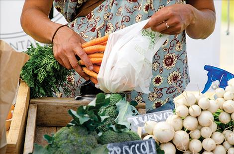 A shopper gathers homegrown food from the St. Ignatius farmers market.
