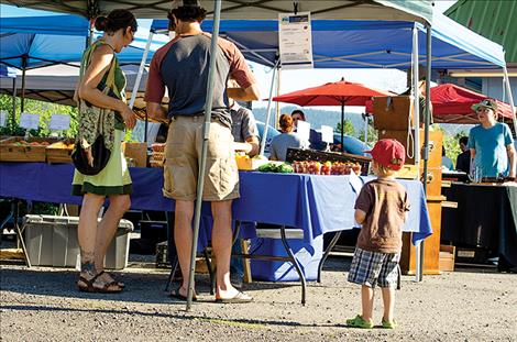 People enjoy recently-picked tomatoes, carrots, greens and other farm-fresh foods as well as  handcrafted items available at the market.