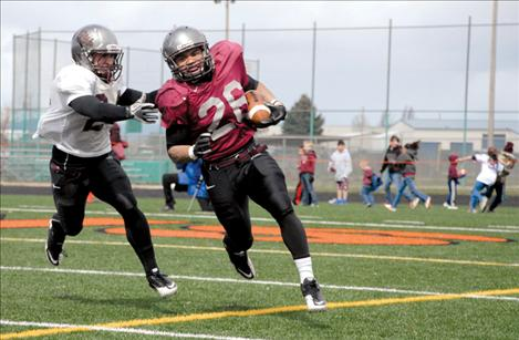 University of Montana junior running back Jordan Canada escapes a teammate during the Grizzlies' spring scrimmage held Saturday at Ronan High School's Laverne Parrish Field.