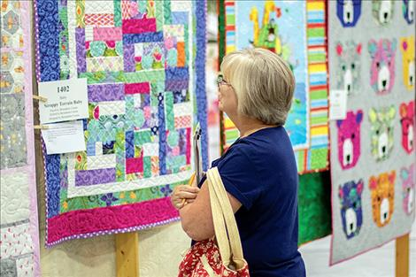 A visitor to the quilt show studies the details of quilt number 1402.