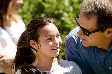 Montana Gov. Steve Bullock visits with a child at the Arlee Community Center on July 24.