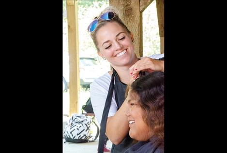 Holly Oakland of Rootz Salon gives one of more than a dozen haircuts during the event.