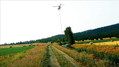 A helicopter bucket dips into an irrigation ditch on the Biggs Ranch.
