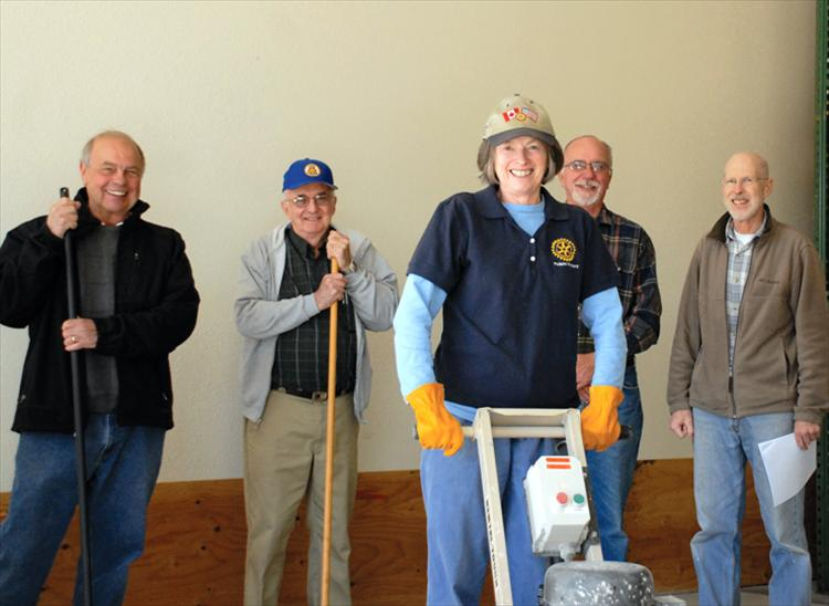 Keith Urbach, Rotary president elect, left, Ken Siler, Rotary president, Jules Clavadetscher, past president, Sharon, Fulton, past president, front, present a check to Bryan River, Loaves and Fish Food Pantry director, for flooring in the receiving area.