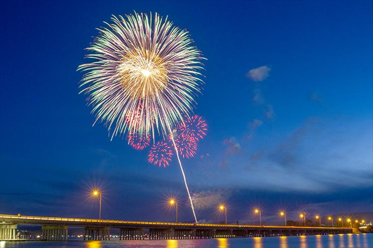 July 4th fireworks rise above the lights of Polson's Veterans Memorial Bridge.
