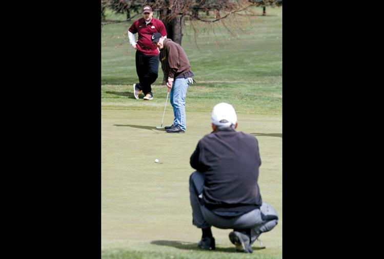 Chad Komlofske of Polson watches his putt roll in as Billy Fisher of Missoula and Ron Fricker of Polson look on.