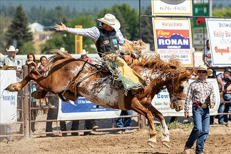 Saddle bronc rider Andrew Evjene holds on for a 78-point first place ride.