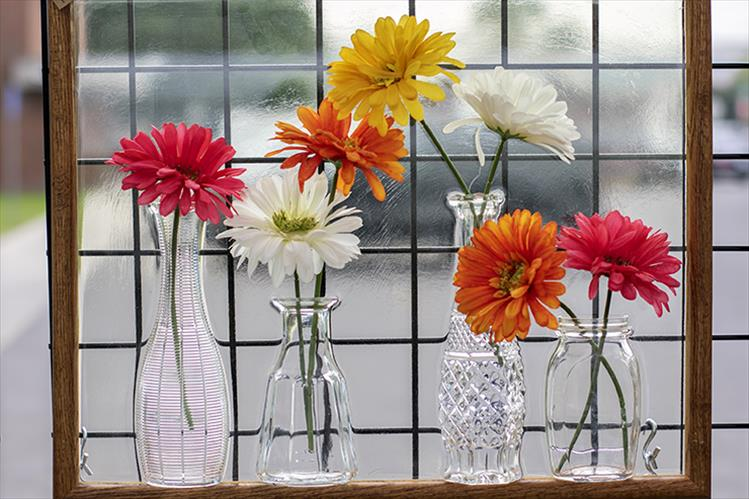 Bright flowers in various shaped vases are framed for display.