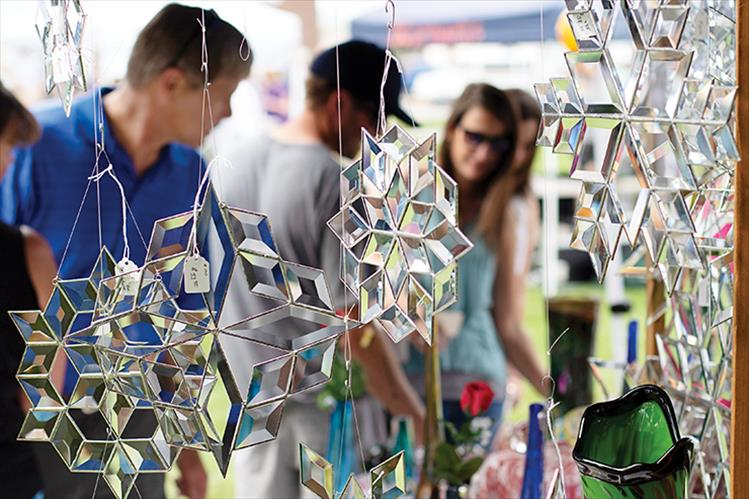 Glass snowflakes hang from an art vendor's booth.