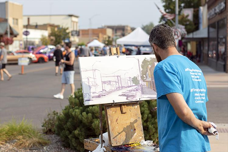 An artist paints Polson's outdoor streetscape during the  simultaneous Summerfest Car Show on Main Street.