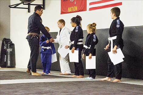Instructor Justin Dumontier congratulates the students for finishing the summer Jiu-Jitsu program.