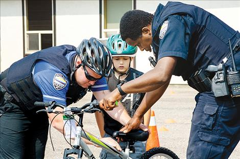 Polson Police Officers Keith Deetz and Hazeez Fafiu lower the seat on a bike so a child can ride it through their safety course during the Back to School  Wellness Fair on Saturday.