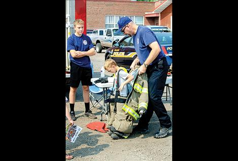 Lt. James McKee with the Polson City Fire Department helps a child try on the gear firefighters wear.