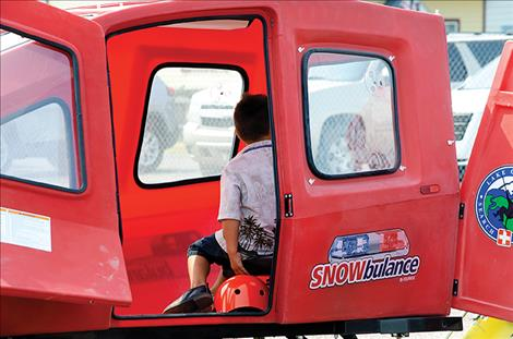 A child gets in the Snowbulance used by the LCSAR to rescue people on trails.