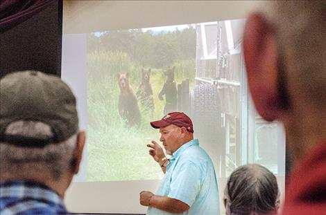 Confederated Salish and Kootenai Tribes Wildlife Biologist Stacy Courville speaks at a meeting in Arlee on Aug. 28 about the conflicts that arise as bears share land with humans on the CSKT Reservation. He points towards a photo of three bears  checking out a trap used to relocate bears.