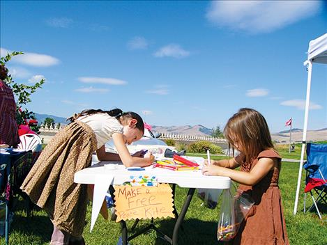 Children make kites at the Flathead Human Rights Coalition table.