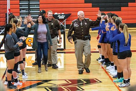 Emergency responders get a high-five from the volleyball teams.
