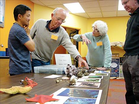 COPUS conference attendees discuss a presentation on tide pool animal adaptations.