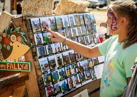 Olivia Cheff points to a photo of one of the 57 decorated hay bales entered in this year's hay bale decorating contest. Community members voted at the Harvest Fest for their favorite.