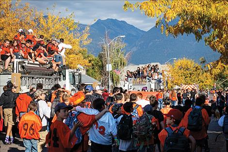 Ronan's Main Street is filled with various shades of orange showing homecoming spirit as parade participants march to the beat of the RHS band.
