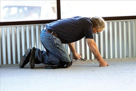 A volunteer installs carpeting Friday for the Boys and Girls Club as part of Community Build Day.