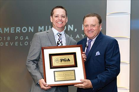 Cameron Milton (left) accepts his award from PGA of America President Paul Levy.