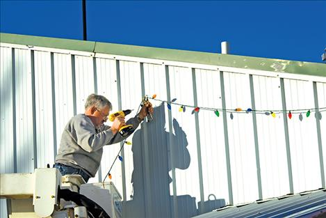 Jay Preston hangs part of thousands of Christmas lights at the Ronan Fairgrounds for the upcoming Lights Under the Big Sky event.