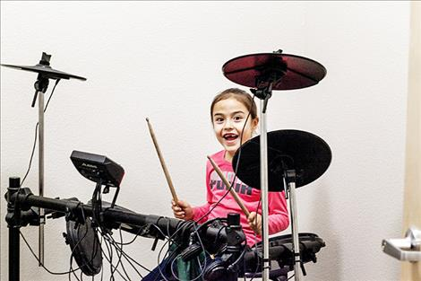 Molly Charlo tests out the drums at the new club's recording studio.