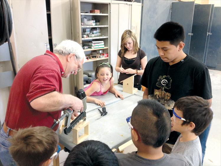 Ronan High School shop teacher Dave Edington does some drill work while his students help Sheila Hoback's first graders make bird feeders last week.