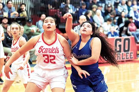 Scarlet Halle Adams and Lady Bulldog Addison Arlint battle for a rebound.