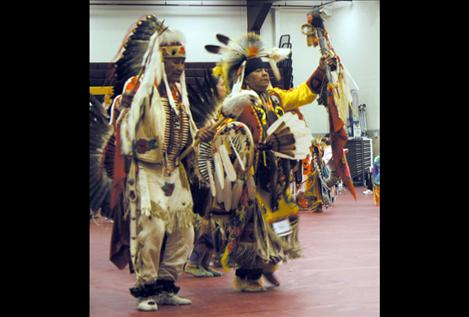 Elder Pat Pierre and his son Alan Pierre dance side-by-side during the opening ceremony Friday night.