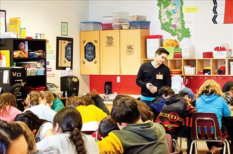 Poet Alex Alviar with the Missoula Writing Collaborative works with a group of Pablo Elementary School students on a poetry writing project.